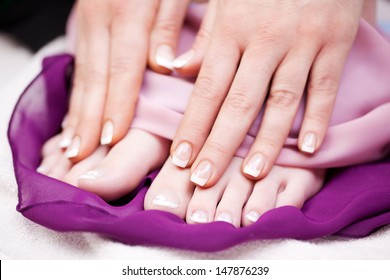 Woman with French manicured finger and toe nails displaying them for the viewer after enjoying a relaxing manicure in a beauty salon