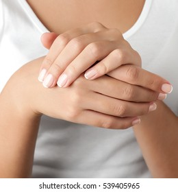 Woman french manicured hands against body in white shirt, close-up. Square composition.