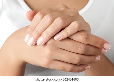Woman french manicured hands against body in white shirt, close-up.