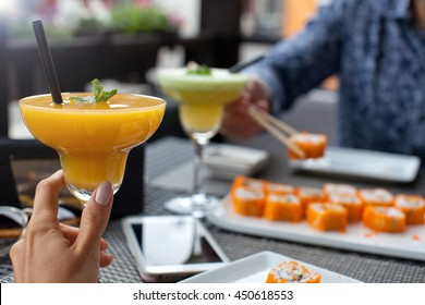 Woman with fresh papaya smoothie in sushi bar on summer day. Food Concept