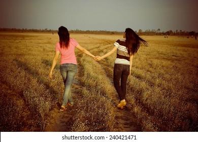 woman friend walking hand in hand going in spring field
