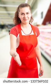 Woman with friendly expression working at hypermarket or supermarket waiting for hand-shake as greeting