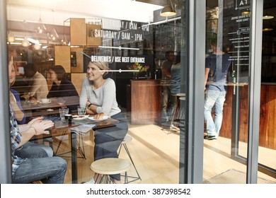 Woman with friends at a cafe seen through window