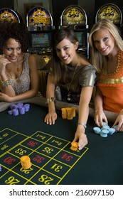 Woman and friends placing gambling chips on roulette table, portrait, elevated view