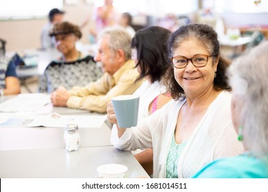 Woman with friends talking and having coffee in a senior center