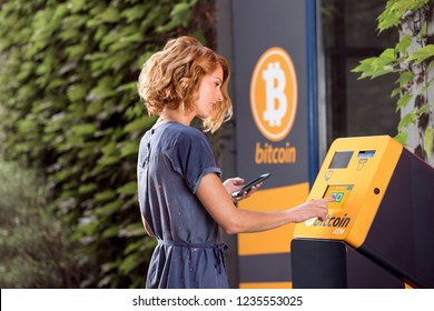 Woman in front of ATM for crypto currency.