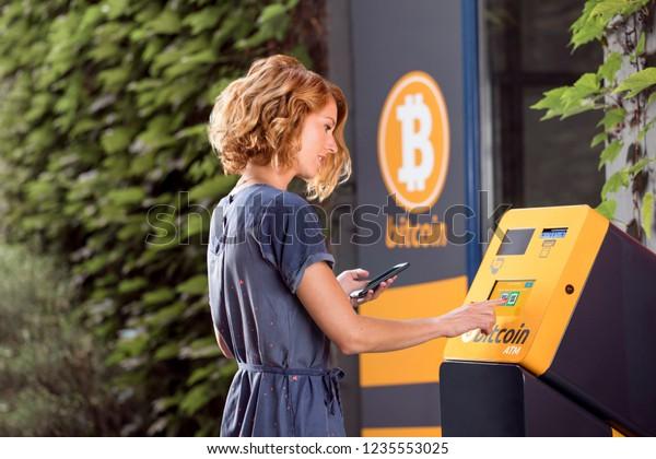Frau vor dem Geldautomaten für Kryptowährung.