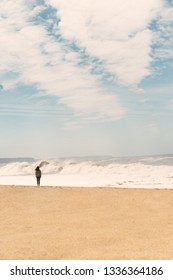 woman in front of big  ocean waves