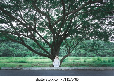 woman in front of the big tree in the park  vintage style in concept lonely , alone nature green earth