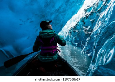 A woman in the front of a canoe stops to appreciate the clear blue ice in the walls of an ice cave. Valdez glacier ice cave in 2016