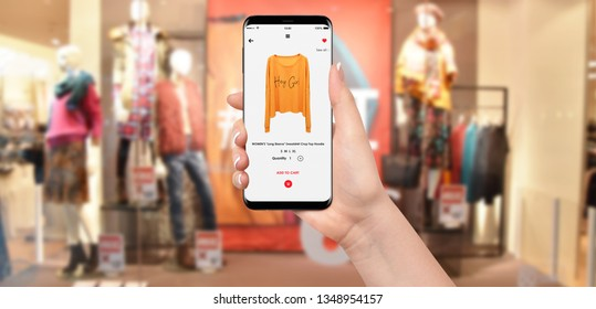 Woman In front of clothing store buying yellow hoodie online on her phone, blurred clothing store in background