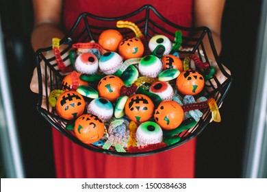 Woman at the front door offering funny Halloween candies on a spiderweb shaped bowl. Unrecognizable person
