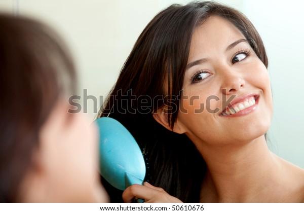 鏡の前の女性が髪を磨く