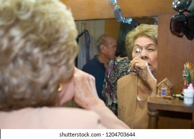 A woman in front of the mirror is getting ready for her 50th wedding aniversary, on bottom of the picture the image of her husband, also getting dress for the love of his life and this great event.