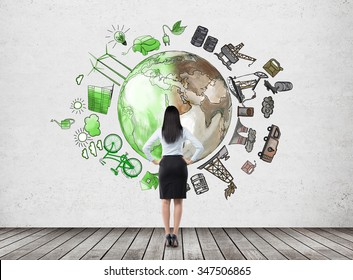 woman in front of the wall thinking about oil production and pollution, brown illustration of oil industry and green eco energy on white wall arranged in circle, concept of environment, back view