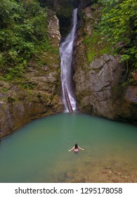 Woman in front of waterfall at a tropical deep jungle of Sabah Borneo.