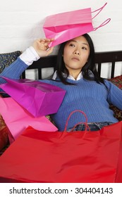 A woman with a frown and shopping bags piled on her.