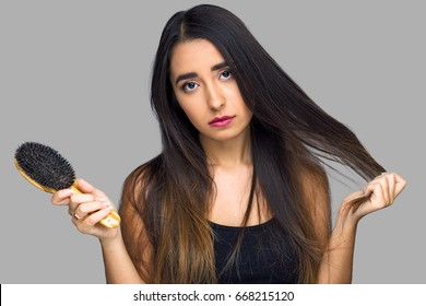 Woman frustrated with unmanageable hair, tangled and dry frizzy damaged flat hairstyle with dead ends