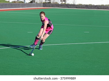A woman a full stretch brings the ball into the circle in a field hockey match.