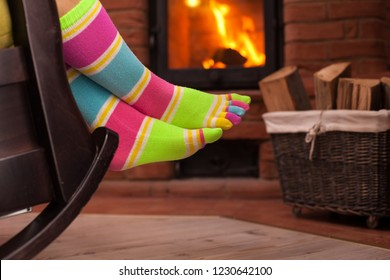 Woman with funny socks relaxing in the evening by the fireplace - closeup