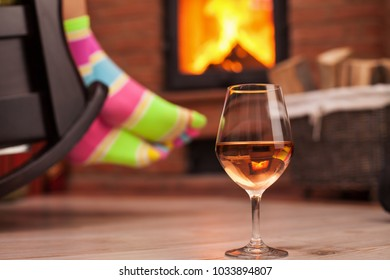 Woman with funny socks relaxing with a glass of wine in front of the fireplace in a rocking chair - closeup, shallow depth