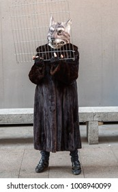 the woman in the fur coat, with animal mask and grille in the hands protesting against the killing of animals in Milan Italy