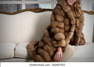 Woman in fur coat, close up, on the sofa, fur texture
