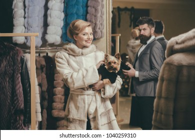 Woman in fur coat with dog and man in shop. Purchase and fashion concept. Couple in love: girl with makeup in luxury mink fur coat and man with wallet. Lady and man with beard on fur coats background.