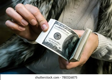 A woman in a fur waistcoat holds a bundle of money in her hands. The symbol of Baghdad.