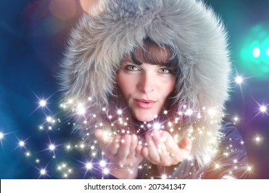 woman with furry hat blowing sparkling stars into the air