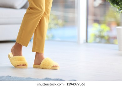 Woman in fuzzy slippers at home, space for text. Floor heating