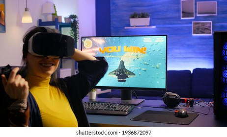 Woman gamer winning space shooter video games while wearing vr headset in gaming studio. Pro player playing video games during online tournament using technology network wireless