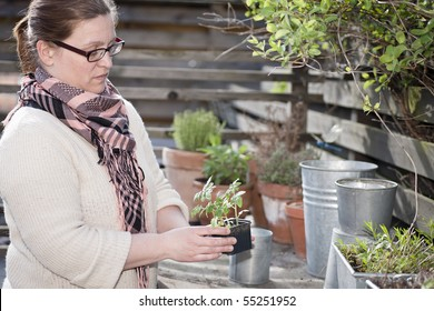 Woman in the garden holding a flower pot with small young plants