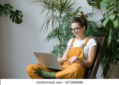 Woman gardener in glasses wearing overalls, sitting on wooden chair in greenhouse, using laptop after work, talks with her friend about coronavirus and stay home during online video call. Working home