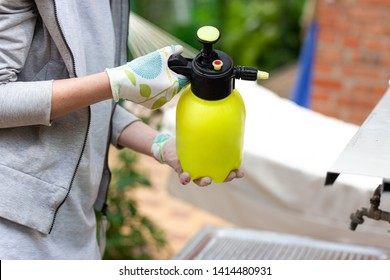 Woman gardener holding a sprayer with pesticide