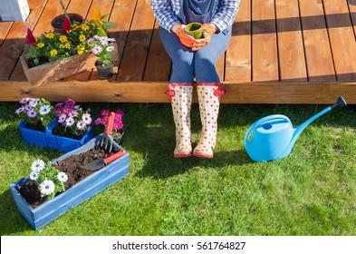 Frau Gärtnerin mit Wellington-Stiefeln hat eine Kaffeepause, während sie im Garten arbeitet, sitzt sie auf Patio-Holzboden