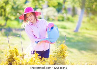 Woman gardening spring summer nature concept. Young smiling woman wearing straw hat with watering can in the garden.