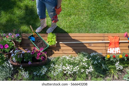 Woman with gardening tools standing on a lawn, flowers and pots around