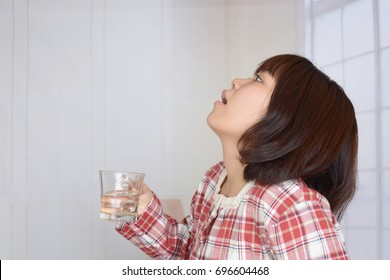 Woman gargling throat in her bathroom at home