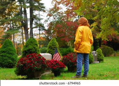 Woman at gaveside in yellow jackt in a fall day