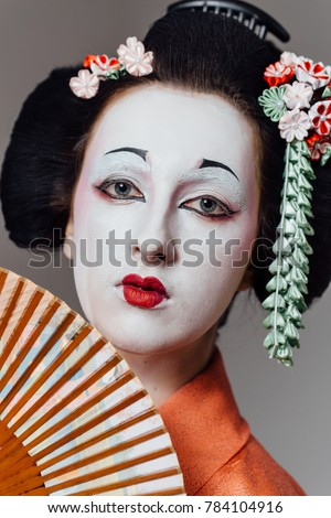 Woman in geisha makeup and a traditional Japanese kimono. Studio, Indoor. Beautiful fan