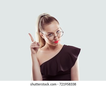 woman gesturing a no sign. Portrait unhappy serious modern style girl raising finger up saying oh no attention do not do that on white light blue background. Negative emotion facial expression feeling