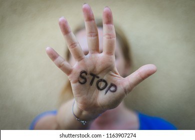 Woman gesturing stop. Selective focus on open females hand with written stop sign. Concept against domestic violence