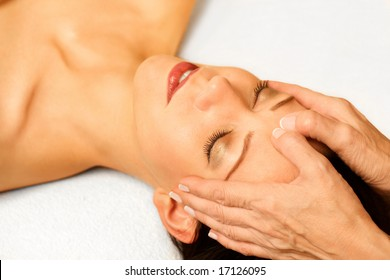 Woman gets facial massage on bright background