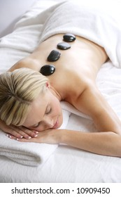 A woman gets a hot stone massage at a day spa