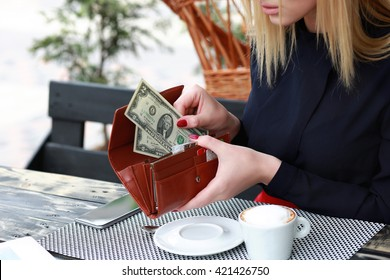 Woman gets money from purse to pay for the coffee. Outdoors, modern cafe.