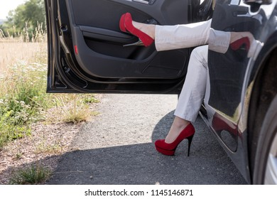 Woman gets out of the car. Legs with sexy red high heeled shoes