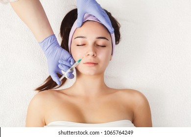 Woman getting beauty facial injections. Anti-aging, nourishing, vitamins treatment at spa salon. Aesthetic cosmetology, top view, copy space