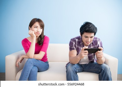 woman is getting bored while man is playing smart phone