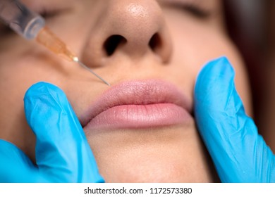 woman is getting botox procedure, doctor is standing near her and holding syringe
